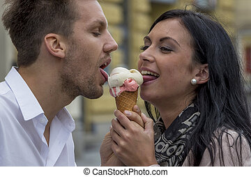 couple eating ice cream - a young couple with a bag of ice...