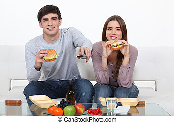 Couple eating junk food and watching television