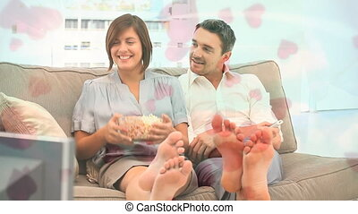 Couple eating pop corn on sofa with pink heart animation