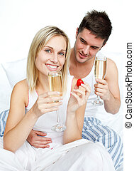 Couple eating strawberries and drinking champagne
