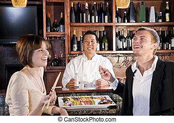 Couple eating sushi in Japanese restaurant