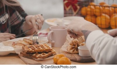 Couple eating their breakfast at a table in a cafe