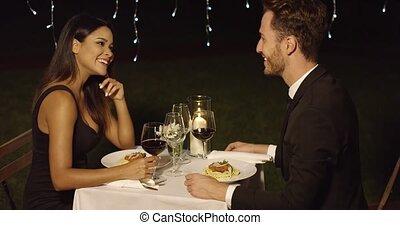 Couple eats spaghetti at fancy outdoor restaurant