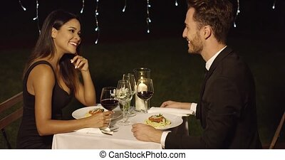 Couple eats spaghetti at fancy outdoor restaurant at night...