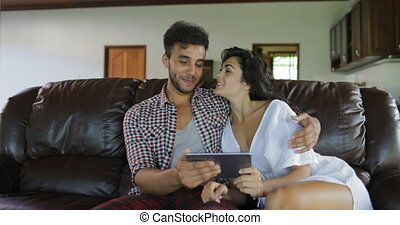 Couple Embrace Sitting On Coach Using Tablet Computer Talking In Living Room, Young Man And Woman Browsing Online Modern Apartment Interior