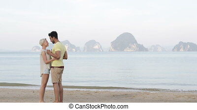 Couple Embrace Standing On Beach, Young Man And Woman In...