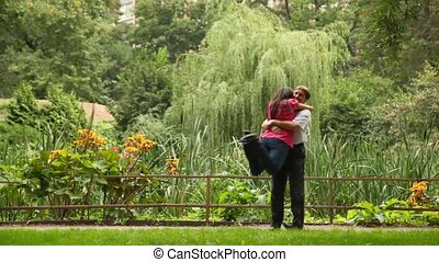 couple embracing and whirling around in garden