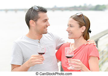 Couple embracing, holding glasses of wine next to river