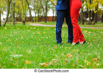 Couple embracing on a green lawn