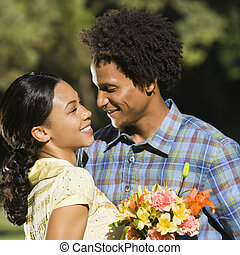 Couple embracing. - Woman holding flower bouquet and...