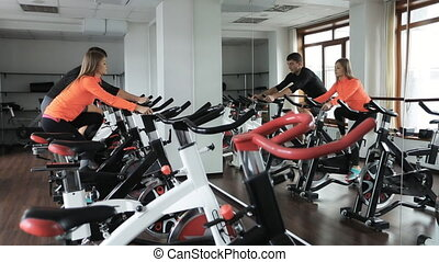 Couple engaged on a stationary bike in gym. They are in gym...