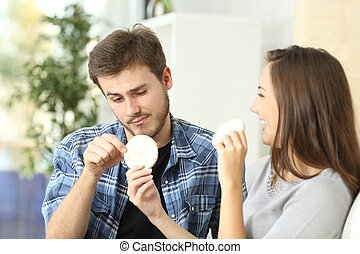Couple enjoying and suffering diet with girlfriend offering...