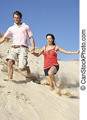 Couple Enjoying Beach Holiday Running Down Dune