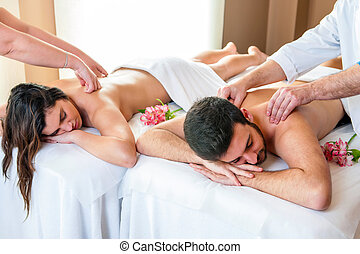 Couple enjoying body massage in spa.