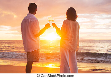 Couple Enjoying Glass of Champene on the Beach at Sunset -...