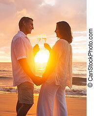 Couple Enjoying Glass of Champene on the Beach at Sunset
