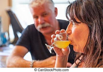 Couple Enjoying Glasses of Micro Brew Beer At Bar.