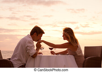 Couple enjoying romantic sunnset dinner on the beach