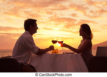 Couple enjoying romantic sunnset dinner - Couple sharing...
