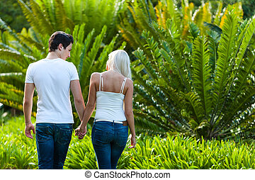 Couple enjoying romantic walk in park.