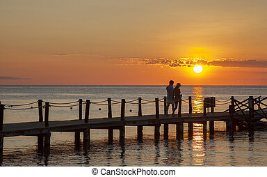 couple enjoying romantic walk on pier by ocean during sunset