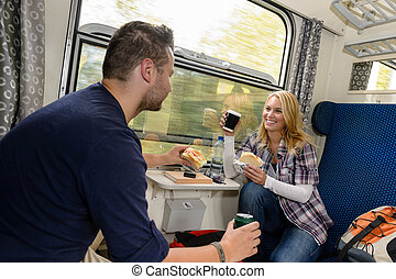 Couple enjoying sandwiches traveling with train smiling...