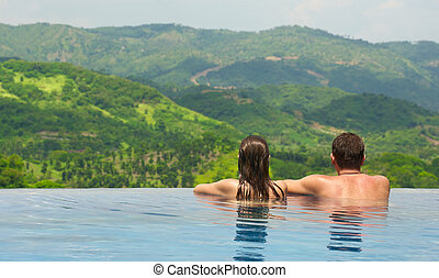 couple enjoying the view of the mountain landscape from pool...
