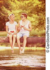 couple enjoying watermelon while sitting on the wooden bridge