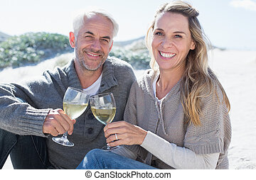 Couple enjoying white wine on picnic at the beach smiling at camera on a bright but cool day