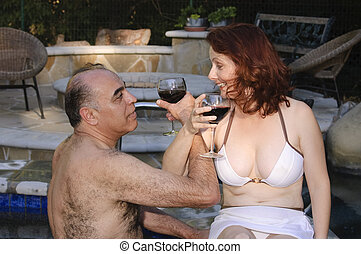 couple enjoying wine by the pool
