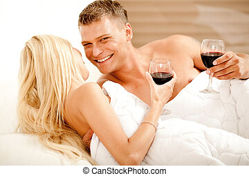 Couple enjoying wine in bed