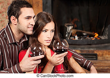 couple enjoying wine near fireplace