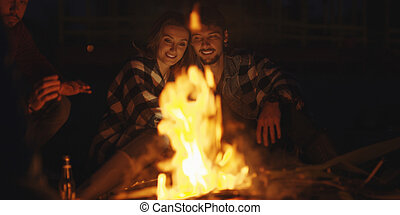 Couple enjoying with friends at night on the beach