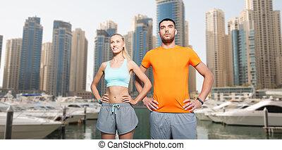 couple exercising over dubai city background