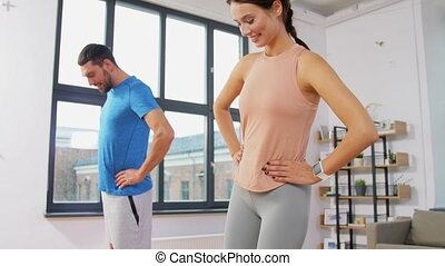 sport, fitness, lifestyle and people concept - smiling man and woman exercising with resistance bands at home