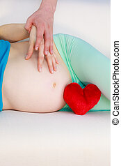 Couple expecting baby, their hands touching pregnant belly