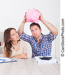 Couple Expecting Money From Piggybank - Woman Looking At...