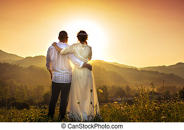 Couple facing romantic sunset in the field