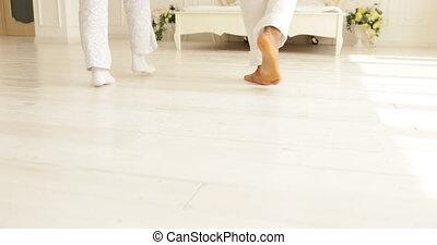 couple feet run jump on bed mix race man woman embrace bedroom