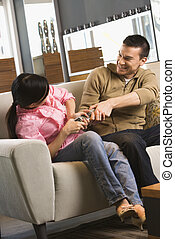 Couple fighting over remote. - Asian couple fighting over...