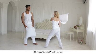 Couple fighting pillows bedroom mix race man woman playing having fun together