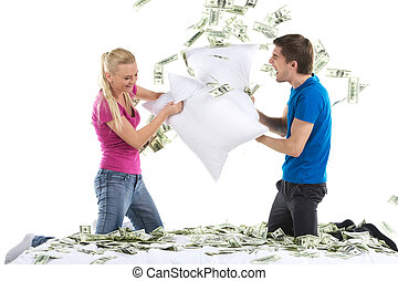 Couple fighting together with pillows in bed. Portrait of happy loving couple with money in bed