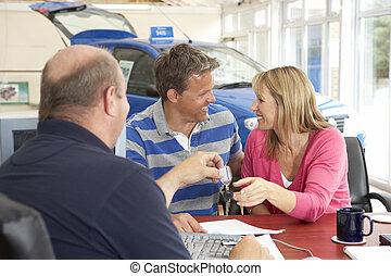 Couple filling in paperwork in car showroom