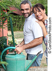 Couple filling up watering can