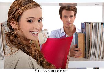 couple, flirter, dans, a, bibliothèque