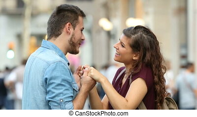Couple flirting and hugging in the street