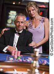 Couple gambling at roulette table