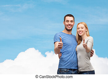 smiling couple showing thumbs up