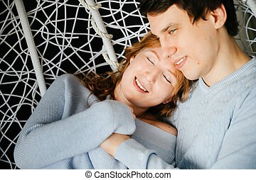 Couple girl and guy hugging on a big chair.