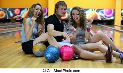 Couple girls with one guy sit on floor and dance at bowling...